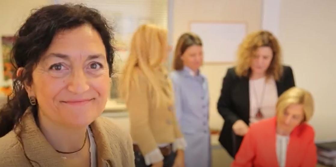 Montse Blasco SL Seguros, con Montse Blasco en primer plano mirando a cámara y el resto del equipo trabajando detrás